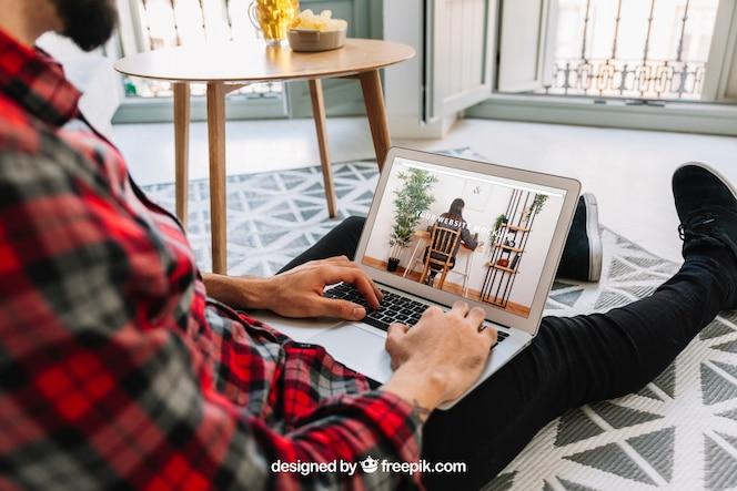 Thuiskantoorconcept met de mens op vloer die laptop met behulp van