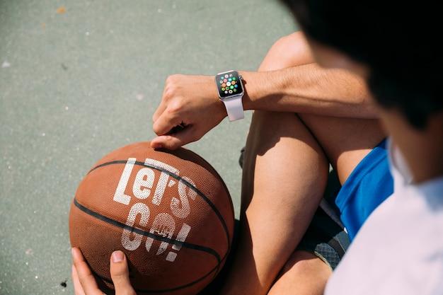 Tiener die een basketbal erachter houdt van