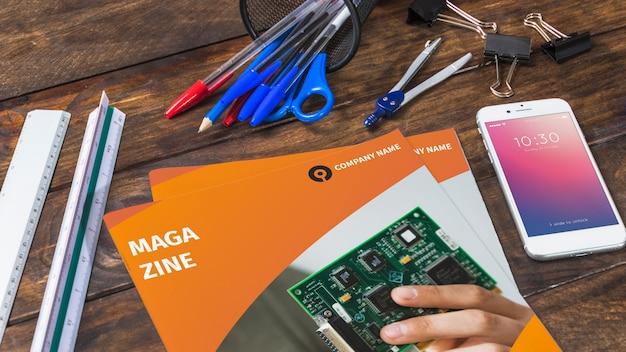 Tijdschrift en smartphone mockup op houten tafel met pennen en linialen