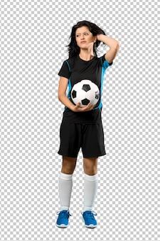 Un tiro de cuerpo entero de una joven futbolista que tiene dudas y confunde la expresión de la cara