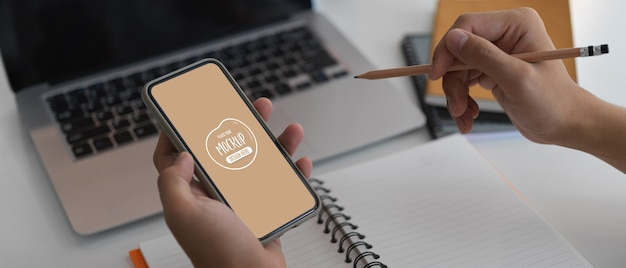 Toma recortada del empresario trabajando en su idea con un teléfono inteligente simulado mientras la escribe