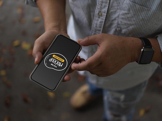 Toma recortada de hombre usando smartphone de maqueta mientras está parado en la calle