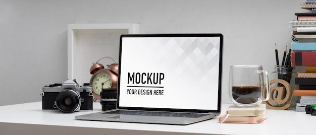 Toma recortada de la mesa de trabajo con maqueta de computadora portátil, cámara, libros y papelería en la sala de la oficina en casa