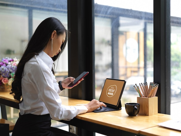 Toma recortada de mujer usando un teléfono inteligente simulado mientras trabaja con una tableta digital simulada en el café
