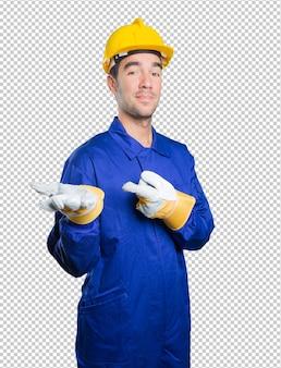 Trabajador confiado con gesto de la demostración en el fondo blanco