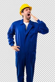 Trabajador joven con el casco que bosteza y que cubre la boca abierta con la mano. expresión somnolienta
