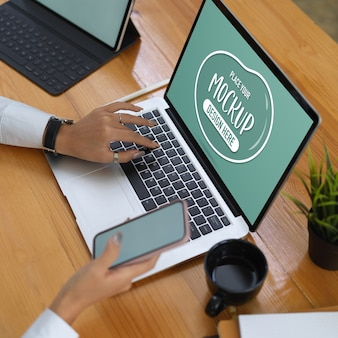 Trabajador de oficina con maqueta de portátil, tableta y suministros