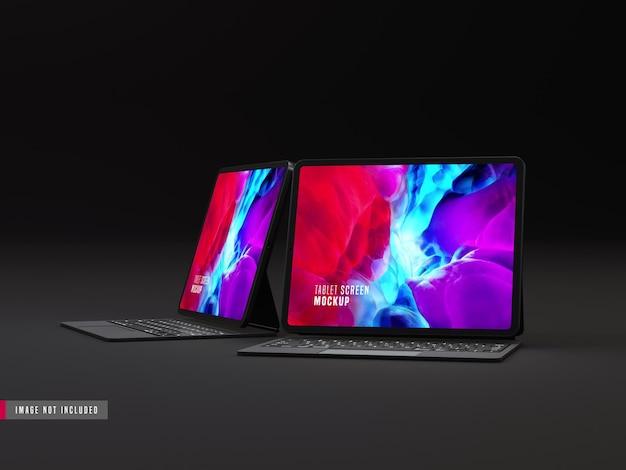 Twee geïsoleerde donkere tablet pro mockup met toetsenbord