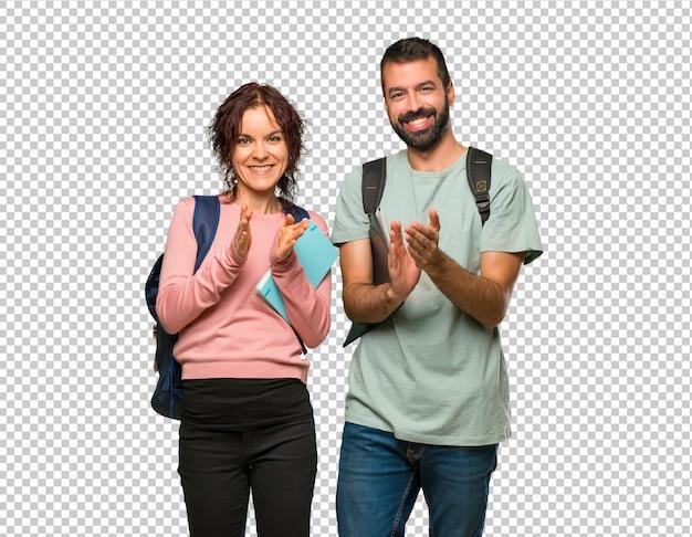 Twee studenten met rugzakken en boeken applaudisseren na presentatie in een conferentie