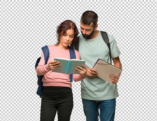 Twee studenten met rugzakken en boeken die een boek lezen