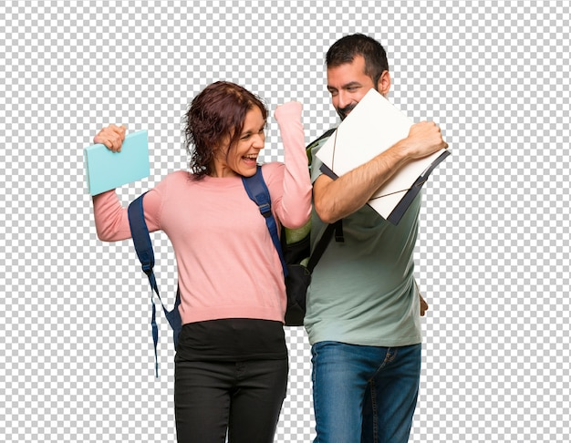Twee studenten met rugzakken en boeken die een overwinning in winnaarpositie vieren