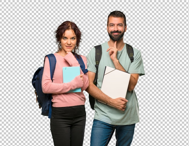 Twee studenten met rugzakken en boeken die en aan de voorzijde met zeker gezicht glimlachen kijken