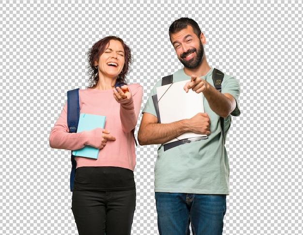 Twee studenten met rugzakken en boeken die met een vinger naar iemand wijzen en veel lachen
