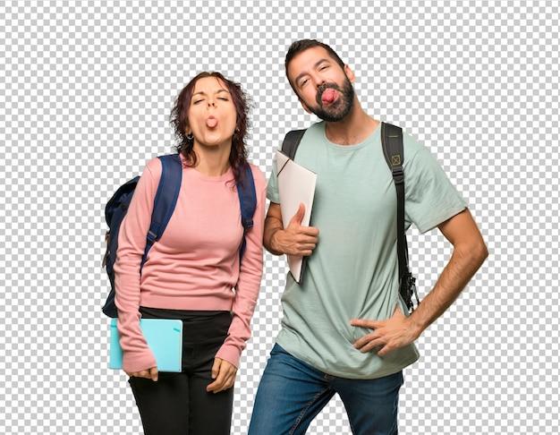 Twee studenten met rugzakken en boeken die tong tonen bij de camera die grappige blik heeft