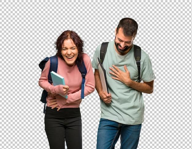 Twee studenten met rugzakken en boeken die veel glimlachen terwijl ze hun handen op de borst leggen