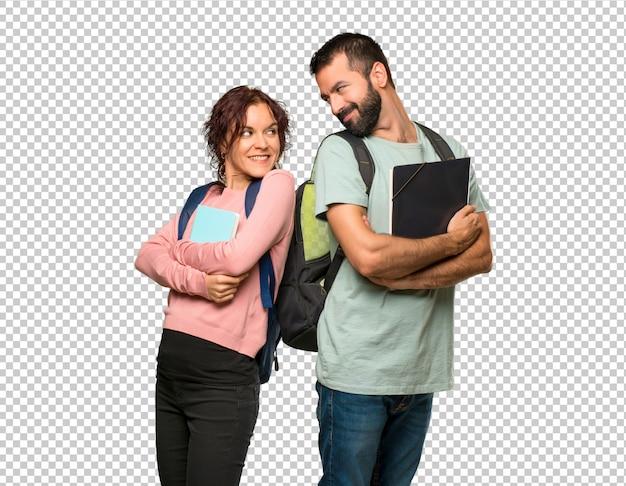 Twee studenten met rugzakken en boeken kijken over de schouder met een glimlach