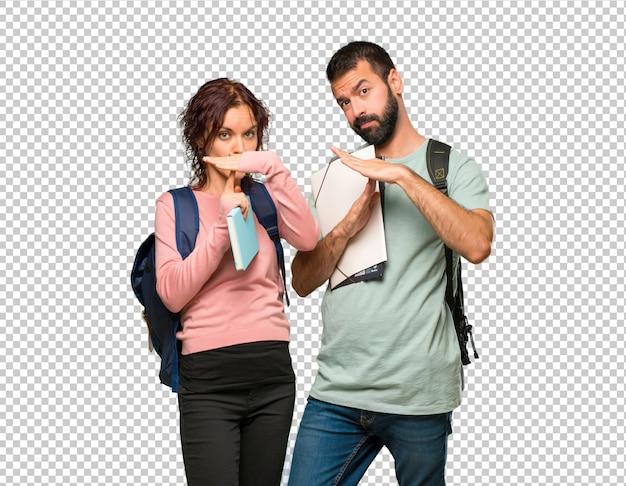 Twee studenten met rugzakken en boeken maken stop gebaar met haar hand om een handeling te stoppen