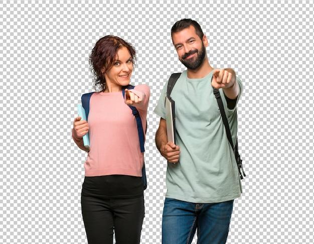 Twee studenten met rugzakken en boeken wijzen je vinger aan met een zelfverzekerde uitdrukking