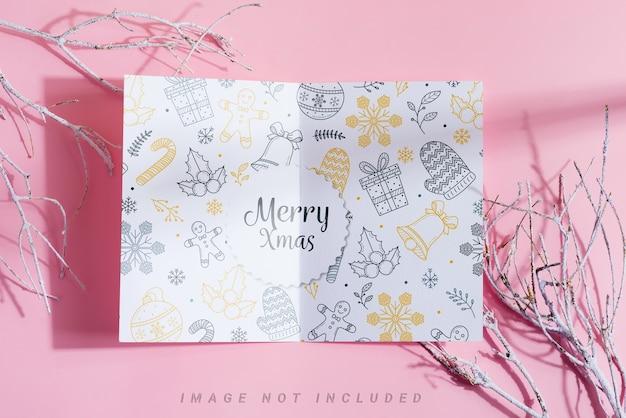 Tweevoudige papieren mock-up brochure en wintertakjes met vorst.