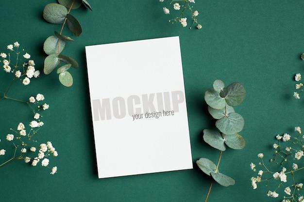 Uitnodiging of wenskaart mockup met eucalyptus en hypsophila twijgen op groen