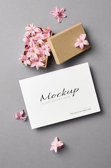 Uitnodiging of wenskaart mockup met roze lentebloemen in doos