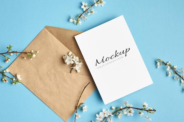 Uitnodiging of wenskaart stationaire mockup met envelop en kersenboom bloemen op blauw