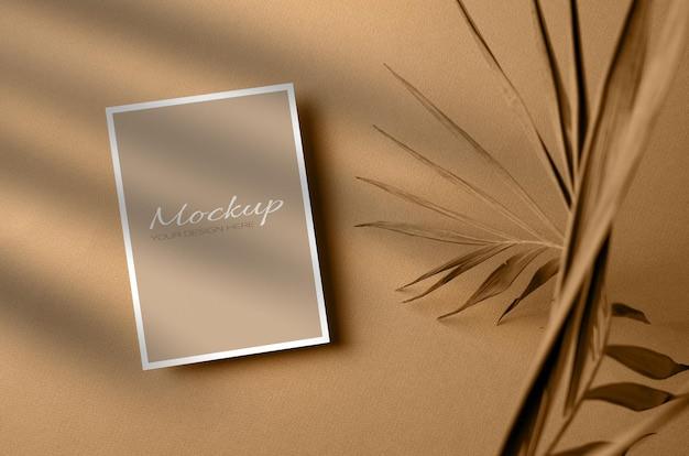 Uitnodiging of wenskaart, stationaire mockup met palmblad van de droge natuur