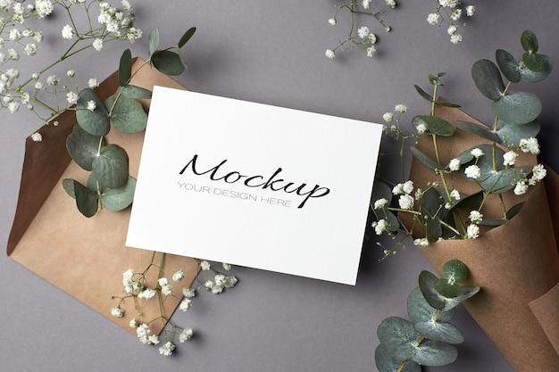 Uitnodiging of wenskaartmodel met envelop en eucalyptus- en hypsophila-bloemen Premium Psd