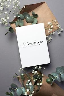 Uitnodiging of wenskaartmodel met envelop en eucalyptus- en hypsophila-bloemen
