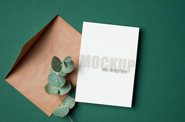 Uitnodiging of wenskaartmodel met envelop en eucalyptustakje op groen