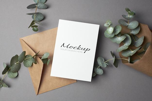 Uitnodiging of wenskaartmodel met envelop en eucalyptustakjes op grijs