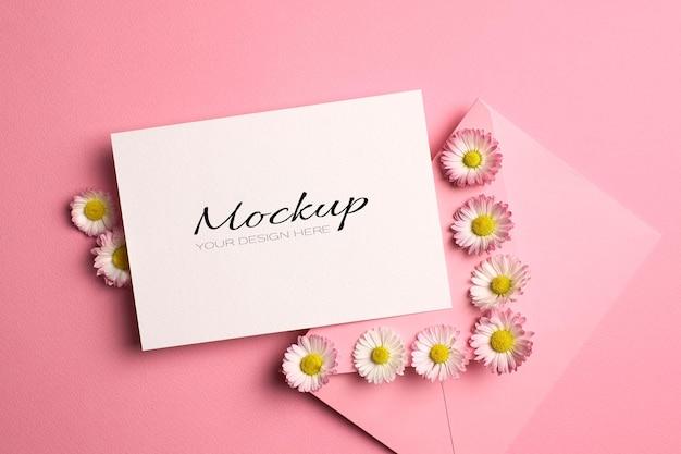 Uitnodiging of wenskaartmodel met envelop en madeliefjebloemen op roze