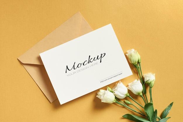 Uitnodiging of wenskaartmodel met envelop en witte eustomabloemen op goud