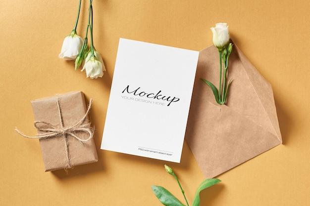 Uitnodiging of wenskaartmodel met envelop, geschenkdoos en witte eustoma-bloemen
