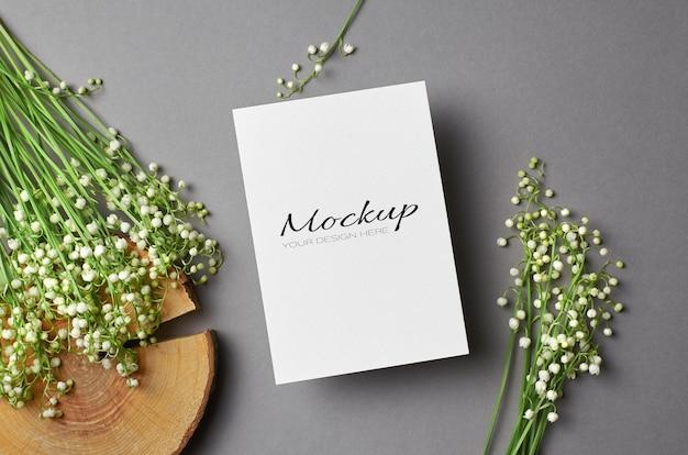 Uitnodiging of wenskaartmodel met lelietje-van-dalen bloemenboeket op gesneden log