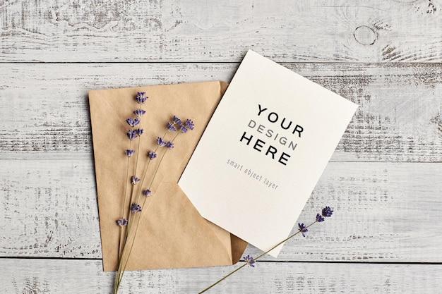 Uitnodigingskaartmodel met envelop en lavendelbloemen op houten achtergrond