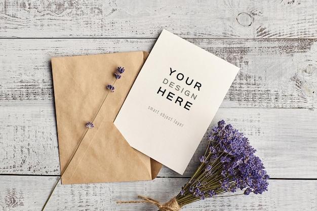 Uitnodigingskaartmodel met envelop en lavendelbloemenboeket op houten achtergrond