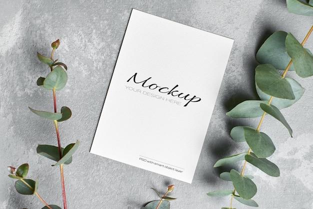 Uitnodigingskaartmodel met verse eucalyptustakjes op grijs