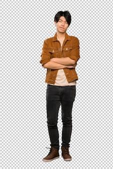 Un colpo di lunghezza di un uomo asiatico con giacca marrone con espressione faccia confusa
