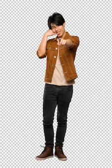 Un colpo di lunghezza di un uomo asiatico con giacca marrone facendo il gesto del telefono e rivolto verso l'alto