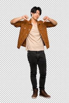 Un colpo integrale di un uomo asiatico con giacca marrone che mostra il pollice verso il basso