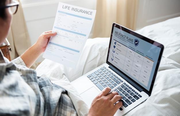 Un uomo che lavora con un computer portatile a letto