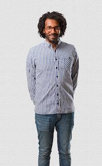 Uomo afroamericano bello di affari allegro e con un grande sorriso, sicuro, amichevole e sincero, che esprime positività e successo