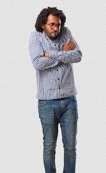 Uomo afroamericano bello di affari che dubita e che scrolla le spalle le spalle