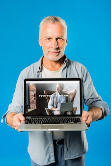 Uomo anziano che presenta il modello di laptop