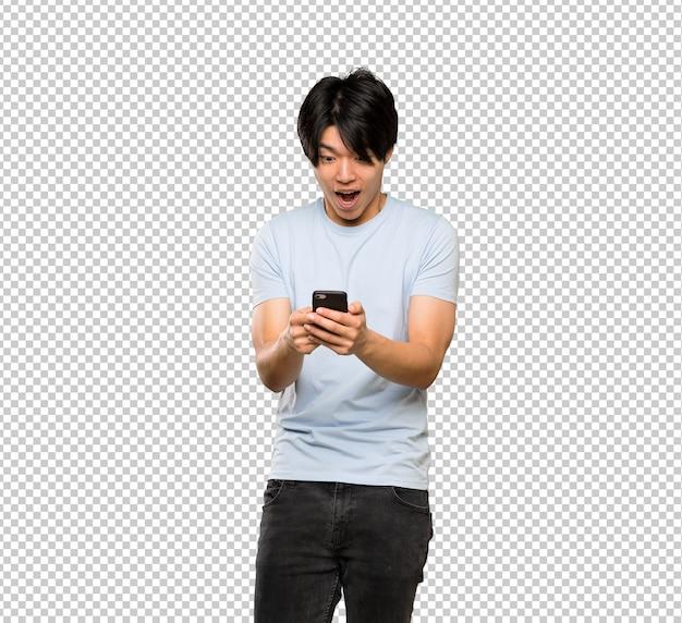 Uomo asiatico con la camicia blu sorpreso e inviando un messaggio