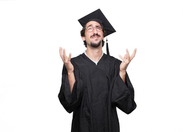 Uomo barbuto laureato con uno sguardo sciocco, sciocco, sciocco, sentendosi scioccato e confuso