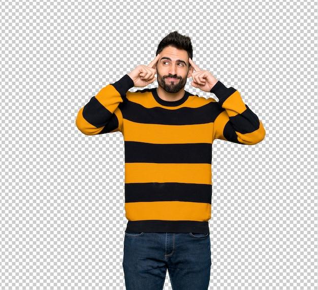 Uomo bello con il maglione a strisce che ha dubbi e pensiero