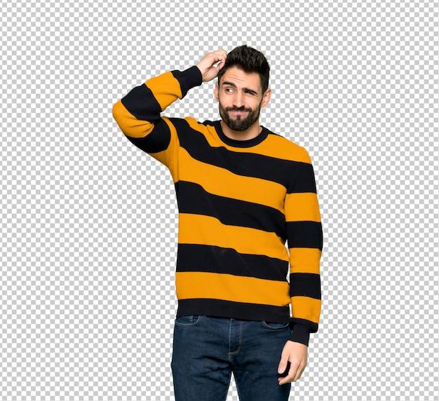 Uomo bello con il maglione a strisce che ha dubbi mentre grattando la testa