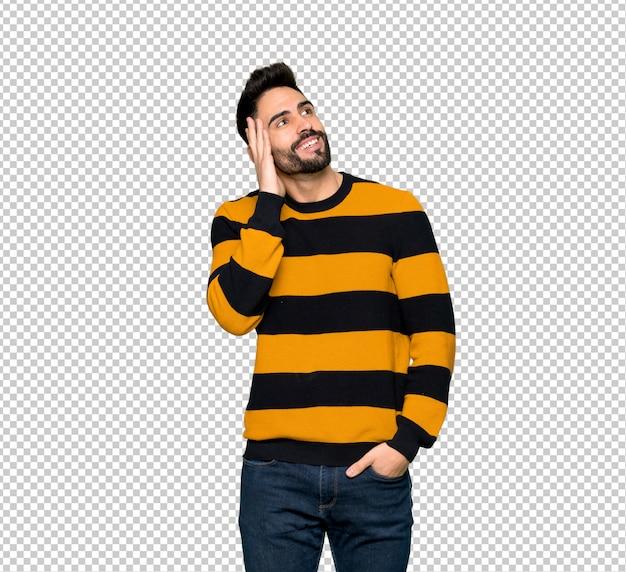 Uomo bello con il maglione a strisce che pensa un'idea mentre graffiando si dirige